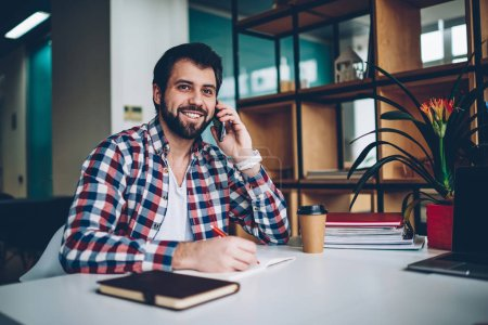 Positive bearded man with mobile phone calling to friends using application, smiling happy young hipster guy looking away while talking via modern cellular indoors, technology and communication