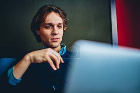 Serious millennial man reading information from web page browsed on laptop computer working on freelance at home, smart hipster guy concentrated on installing new app on netbook for distance jo