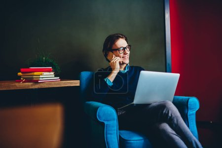 Photo for Cheerful hipster guy talking on cellular while sitting in comfortable chair with laptop computer, smiling millennial man having mobile phone conversation satisfied with remote job at home interio - Royalty Free Image