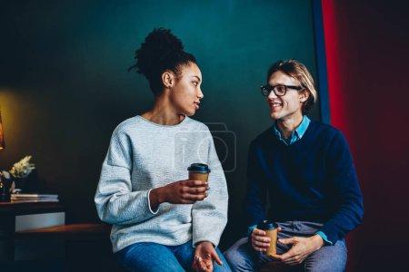 Couple multiracial parler les uns aux autres, assis avec des tasses à café, positives amis masculins et féminins, discuter des idées et des opinions de la part pendant la pause au bureau, gai homme regardant collègue