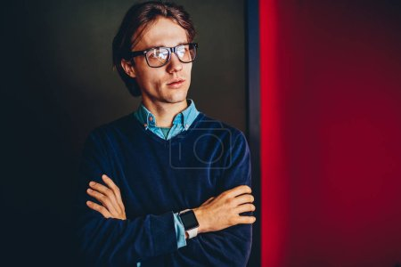 Pensive young male entrepreneur in spectacles for vision correction thinking about idea for startup project looking away,thoughtful businessman with crossed arms and smartwatch standing indoor