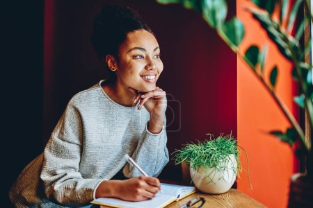 Smiling beautiful dark skinned woman writing article in notebook for publication  in blog looking in window, positive hipster girl dreaming about vacations noting plans in notepad on leisur