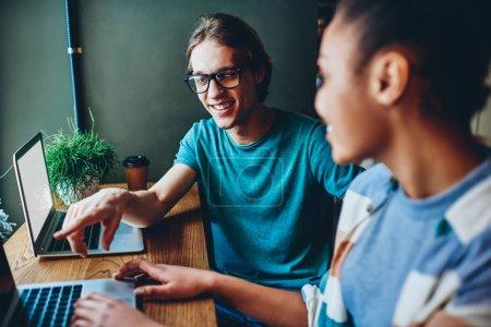 Photo pour Joyeux caucasien mâle dans les lunettes pointant sur ordinateur portable satisfait de travail à distance avec une collègue féminine, étudiants multiraciaux discuter des idées pour le contenu Web assis ensemble dans caf - image libre de droit