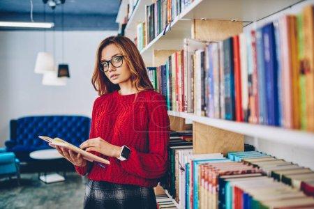Halblanges Porträt eines charmanten Hipster-Mädchens mit Brille zur Sehkorrektur, das Zeit mit Literatur verbringt und neben Bücherregalen in der Bibliothek steht, Konzept von Wissen und Bildung