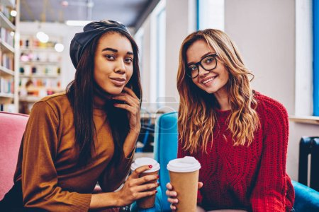 Portrait of successful multicultural hipster girls looking at camera and enjoying coffee break indoors, happy smiling female teenagers in trendy apparel holding takeaway cup at campus on leisure