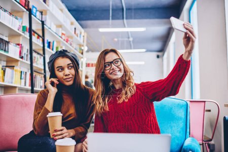 Two happy hipster girls posing and making selfie photos on front smartphone camera sitting at bookstore with takeaway coffee, positive smiling female teenagers taking pictures on mobile phone