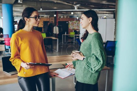 Young female colleague having conversation about business during work break in office, serious woman executive manager talking to woman employee about project creation checking results of work
