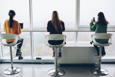 Back view of young women sitting at table near big window in loft interior coworking space, female using modern technology and wireless connection addicted to gadgets and ignore real communication