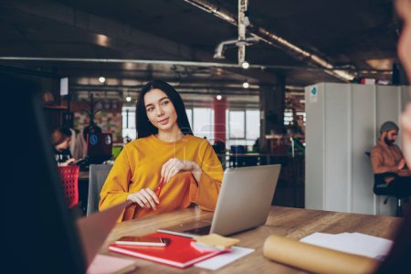 Positive brunette woman sitting at desktop pondering on creative idea for project, attractive dreaming female employee thinking about article for publication working in modern office with wifi