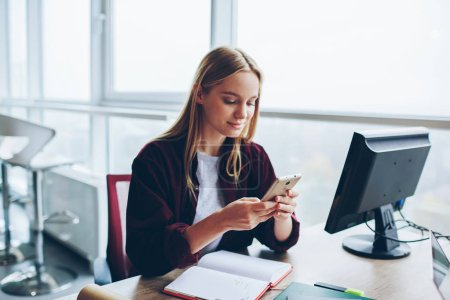 Positive blonde female blogger sending text message in social networks using smartphone, caucasian women sitting at desktop in office using mobile phone for chatting and checking mail via wifi