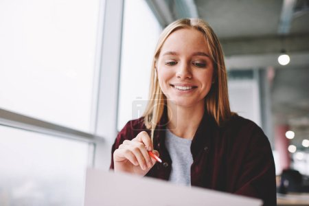 Positive blonde woman fill in information in questionnaire making application for hire on vacancy, smiling female students satisfied with know answers for test completing writing with pen indoors
