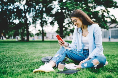 Young woman in casual wear recreating on spring day in park making video call to friend via 4G connection, smiling hipster girl checking social networks updates sitting on green grass with cellular