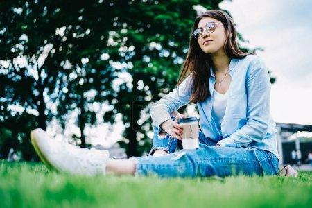 Photo pour Femme brune pensive en tenue décontractée assise sur l'herbe verte rêvant de quelque chose sur le temps de loisirs, étudiante réfléchie dans des lunettes détournant les yeux recréant sur la pause café sur le campus - image libre de droit