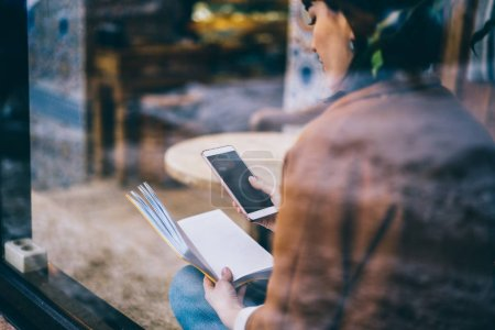 Millennial hipster girl holding smartphone device with mock up screen during reading literature at cafeteria, young brunette woman communicated via modern mobile phone connected to wifi indoors