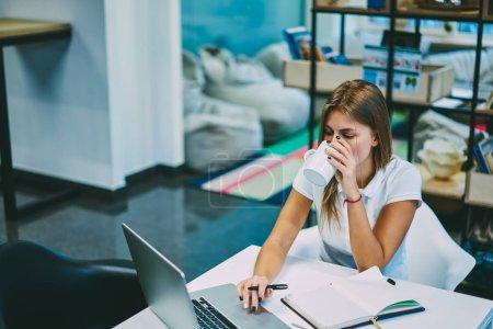 Photo pour Jeune femme buvant un café savoureux tout en recherchant des informations sur les sites Web et faire des devoirs en utilisant Internet sans fil sur ordinateur.Étudiant hipster pensif profiter de boisson regarder webinaire sur ordinateur portable - image libre de droit