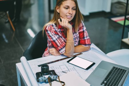 Thoughtful positive young woman in casual wear sitting at desktop with architectural blueprint and modern laptop device in office.Pondering hipster student using digital touch pad with copy space