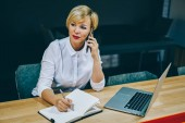 Gorgeous mature female entrepreneur calling with operator on smartphone and writing down text information in notebook working at digital laptop computer.Businesswoman 50 years old talking on cellular