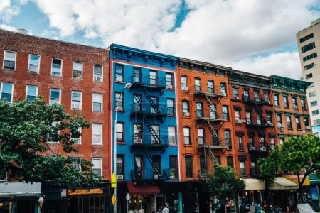 Beautiful cityscape of vintage colourful building with fire escape from residential flats and commercial real estate on ground floor,old houses in Brooklyn district with rental apartments for livin