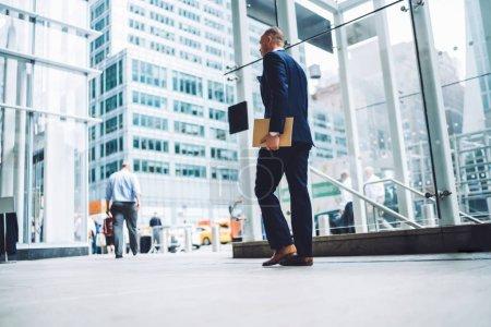 Foto de Vista trasera del hombre de negocios acertado vestido con elegante traje sosteniendo la carpeta con los documentos y va en pasillo de edificio de oficinas. Empresario en ropa formal paseando en compañía financiera - Imagen libre de derechos