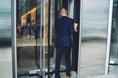 Back view of experienced businessman dressed in elegant suit come into office building via glass door.Male entrepreneur in formal wear going in financial company