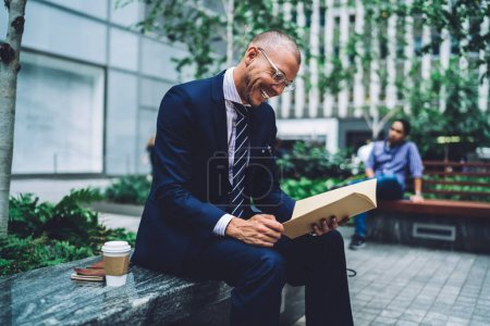 Cheerful professional manager dressed in formal wear reading financial reports in folder and laughing sitting outdoors in urban setting.Positive proud ceo having fun checking documents during break