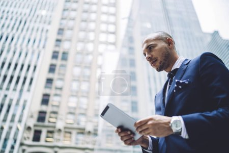 Side bellow view of confident experienced entrepreneur dressed in formal wear searching information on website on modern touch pad using 4G internet in modern business city with high skyscrapers