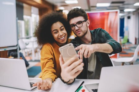 Positive african american hipster girl together with cheerful caucasian young man dressed in casual wear smiling at front camera of modern smartphone and making selfie for publication in internet blog