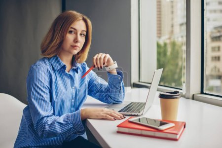 Portrait of blonde businesswoman looking at camera while sitting at modern laptop computer and updating app using wireless internet connection.Successful female graphic designer working on freelance