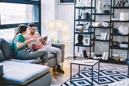 Photo pour Femme pensive avec livre de littérature en mains regardant à réserver des billets mari sur site le dispositif de pavé tactile numérique avec connexion internet sans fil et de détente à la maison avec un intérieur moderne - image libre de droit