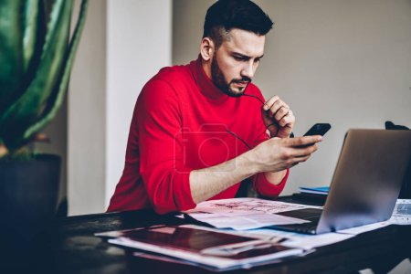 Photo for Pensive young man reading incoming notification on smartphone while working on freelnace at modern laptop computer at home interior.Male blogger updating profile on telephone device using 4G internet - Royalty Free Image