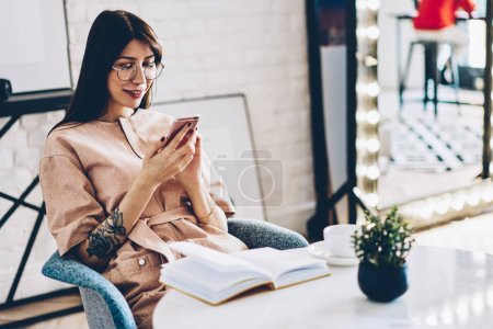 Positive female blogger chatting with followers on modern smartphone device using wireless 4G internet relaxing at home comfort.Cheerful young woman reading funny notification on telephone device
