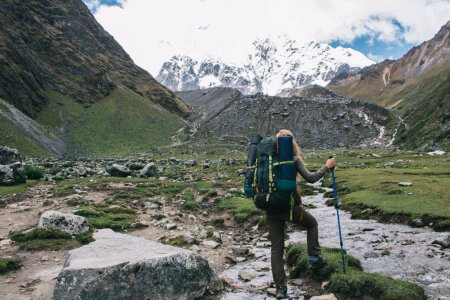 Back view of female tourist with big backpack during hiking trekking in Salkantay mountains on weekend.Rear view of traveler with rucksack admiring amazing scenery of hills in Peru during wanderlust