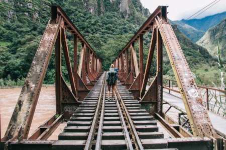 Back view of young woman tourist with backpack discover new places in wildness environment crossing bridge with rails over river.Hiker with travel rucksack going in mountains during trek