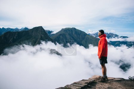 Photo for Experienced male tourist dressed in active wear enjoying calm and inspiration of high green mountains covered white fog standing on edge of summit.Young man traveler admiring breathtaking view - Royalty Free Image