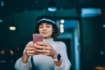 Selective focus on female hands with smartphone, hipster girl holding mobile phone and reading notification, millennial woman updating publication in social networks connected to university wifi