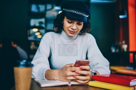 Young millennial hipster girl typing text message and reading funny news on content while browsing internet on mobile phone, trendy woman updating profile in social networks on smartphone device