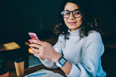Photo for Portrait of smiling female blogger wear in trendy spectacles for provide yeys protection holding mobile phone and checking updates on smartphone, happy hipster girl with curly hair messaging online - Royalty Free Image