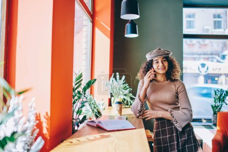 Trendy hipster girl standing near table at cafeteria communicated with friend via telephone call, portrait of cheerful woman making positive conversation using smartphone and 4g internet indoors