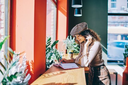 Photo for Trendy smiling female writer in stylish look creating new chapter for book standing at cozy cafeteria, positive hipster girl using notebook for course work spending free time at university campus - Royalty Free Image