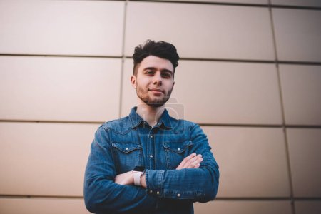 Half length portrait of handsome bearded hipster guy in casual wear and trendy hairstyle standing on wall background, serious young man looking at camera posing with crossed arm feeling confidence