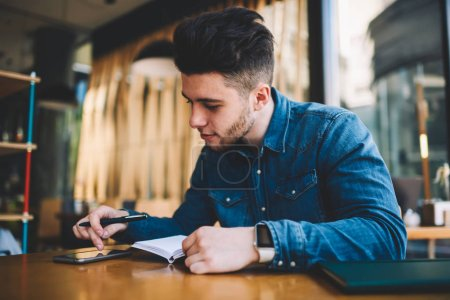 Young male student using smartphone for browsing information and making notes while sitting at cafe interior, concentrated hipster guy writing plans in notepad using organizing apps on cellular