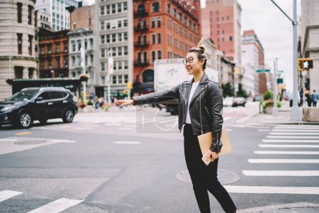 Attractive prosperous asian female blogger dressed in casual clothes trying to catch taxi while walking at spring street.Emotional hipster girl gesturing for stopping public transport outdoors