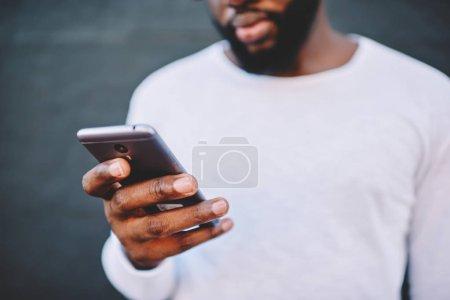 Foto de Recortar imagen de hombre sosteniendo smartphone moderno número de marcación, oscuro de piel hombre afroamericano en camisa blanca usando el teléfono móvil para chatear en redes sociales vía 4g internet conexión fuera de casa - Imagen libre de derechos