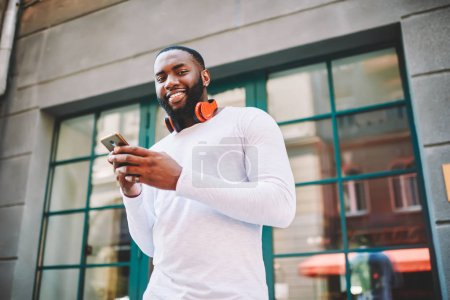 Portrait of handsome african american guy with headphones standing on street using modern mobile telephone,smiling dark skinned male looking at camera while checking mail via smartphone outdoors
