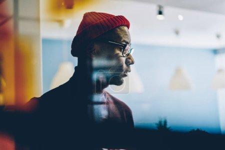 Photo pour Hippocrate africain sérieux dans des lunettes regardant la fenêtre méditant sur des idées au bureau, jeune homme d'affaires rêveur à la peau foncée en tenue décontractée et chapeau concentré sur la planification - image libre de droit