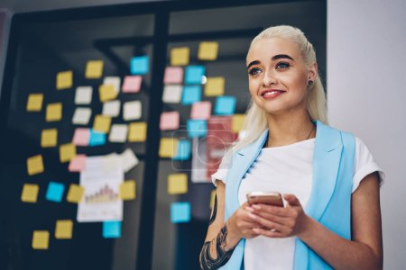 Photo for Pretty blonde caucasian woman standing in coworking space smiling and holding mobile phone, female student satisfied with internet connection in college using smartphone for chatting onlin - Royalty Free Image