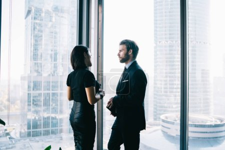 Photo for Male and female entrepreneurs dressed in elegant apparel communicating about projest ideas near window while waiting business partner for cooperation, confident proud ceo in office building - Royalty Free Image