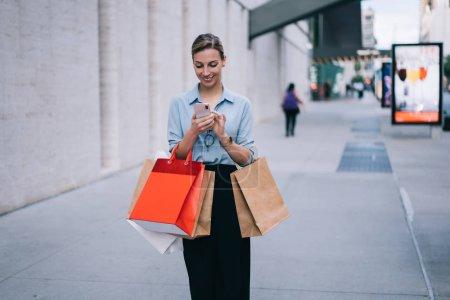 Photo pour Femme caucasienne joyeuse blogueur publication dans le réseau social en utilisant une connexion Internet de 4 g sur téléphone mobile, fille hipster heureuse avec des paquets de magasinage messagerie avec un ami par smartphone - image libre de droit
