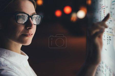 Photo pour Moniteur numérique avec carte du métro. Femme debout à grand écran avec une technologie innovante avancée. Jeune femme touchant avec un écran sensible aux doigts tout en choisissant une option de surface - image libre de droit