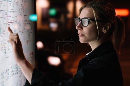 Photo pour Kiosque interactif avec carte du métro. Femme debout à grand écran avec une technologie innovante avancée. Jeune femme touchant avec un écran sensible aux doigts tout en choisissant une option de surface - image libre de droit